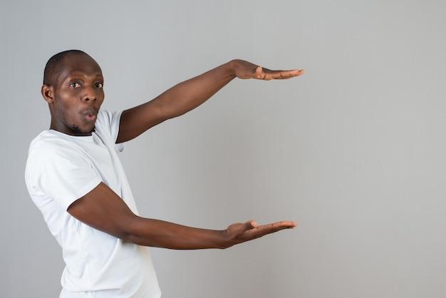회색 벽에 열린 공간을 들고 흰색 티셔츠를 입은 어두운 피부 남자의 초상화