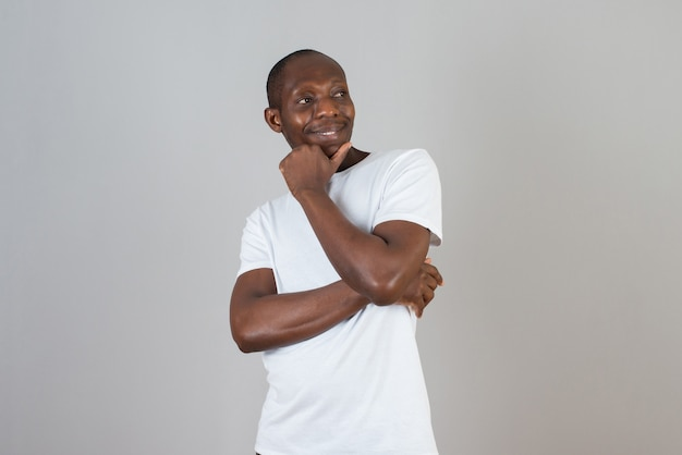 灰色の壁に交差した白いtシャツ立っている腕の暗い肌の男の肖像画