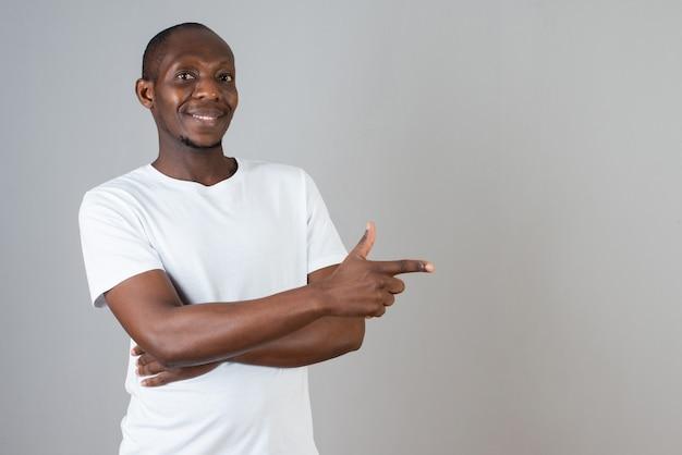 회색 벽에 서 있는 흰색 티셔츠를 입은 어두운 피부 남자의 초상화