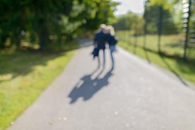 화창한 날에 녹색 무성한 나무의 경로를 따라 공원에서 산책하는 defocused 부부의 초상화