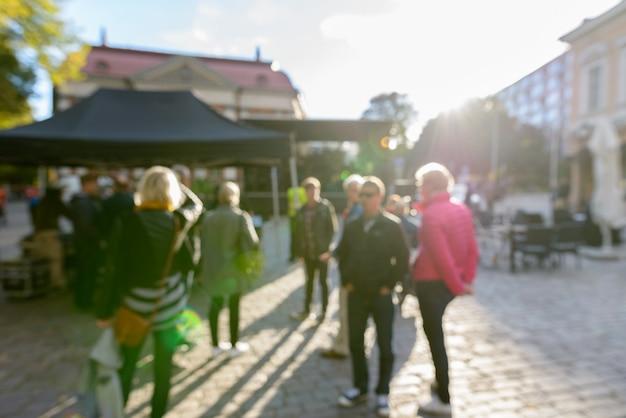 화창한 날에 거리에서 검은 캐노피 앞에서 바쁜 사람들의 defocused 군중의 초상화