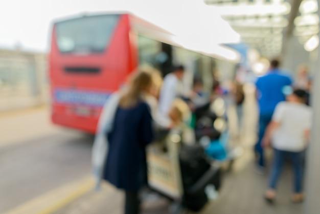 空港の公共交通機関のバスターミナルで焦点がぼけた人々の肖像画