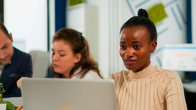 다양한 팀이 통계 데이터를 분석하는 동안 바쁜 시작 사무실의 책상에 앉아 노트북으로 좋은 소식을 읽고 있는 기뻐하는 아프리카 비즈니스 여성의 초상화. 새 프로젝트에서 작업하는 다민족 팀