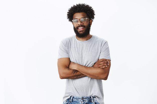 Портрет восхищенного спокойного и красивого афроамериканского коллеги-мужчины в очках с татуировками и пирсингом в носу, радостно улыбающегося и держащего руки, скрещенные на груди, в уверенной позе, говорящей