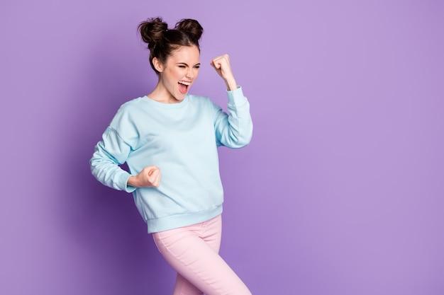 喜んでエネルギッシュな女の子のチャンピオンの肖像画は幸運なコロナウイルスの勝利のニュースを祝う拳を上げるええ、紫色の背景の上に分離された格好良い服を着る