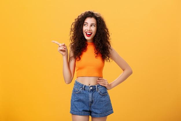 赤い口紅の巻き毛の髪型とクロップドトップを腰に向けて手をつないで、オレンジ色の背景の上に面白くて幸せそうに見える、喜んで熱狂的なスタイリッシュな若い女性の肖像画。