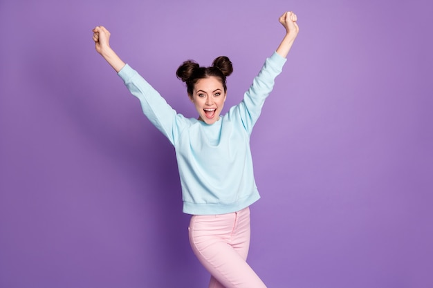 喜んでいる女の子の若者の肖像画はコロナウイルスを楽しんでいます幸運な勝利は拳を上げますええ、紫色の背景の上に分離された格好良いズボンを着用してください