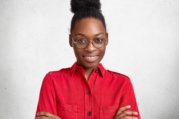 어두운 피부를 가진 기쁘게 행복 부지런한 여성 학생의 초상화, 성공적인 시험 통과에 자신감을 가지고 손을 교차 유지