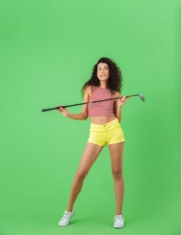 녹색 벽에 서서 클럽을 잡고 골프를 치는 여름 옷을 입은 20대 여성의 초상화