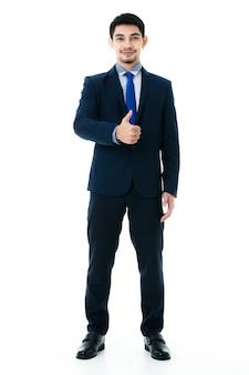 Портрет восхищенного молодого азиатского бизнесмена показывает палец вверх на изолированной белой предпосылке. студия выстрел, бизнес и концепция успеха.