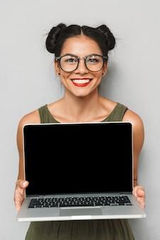 孤立した喜んでいる若い女性の肖像画、空白の画面のラップトップを示しています