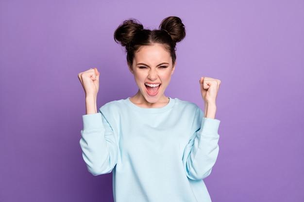 喜んでいる若い女の子の肖像画は、コロナウイルスの勝利のお祝いを楽しんでください拳を上げるええ、紫色の背景の上に分離された格好良い服を着てください
