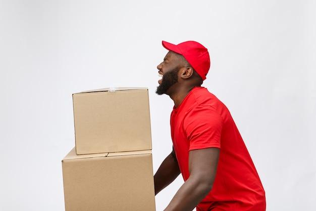 Портрет доставки афро-американский мужчина в красной рубашке. он поднимает тяжелые ящики