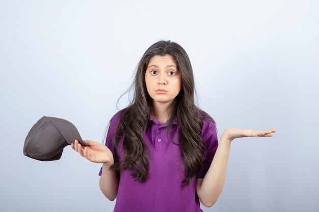 悲しそうな顔で立っている紫色の制服を着た配達の女の子の肖像画。高品質の写真