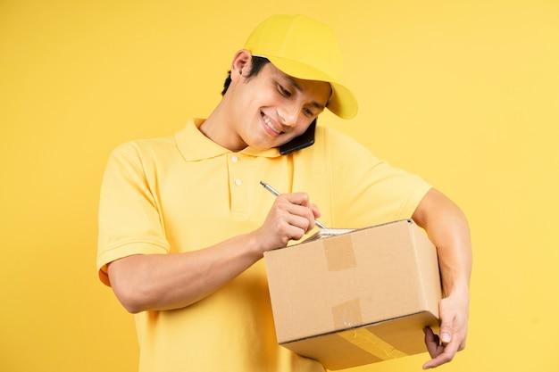 貨物ボックスを保持し、黄色の壁に電話を使用して配達男性の肖像画