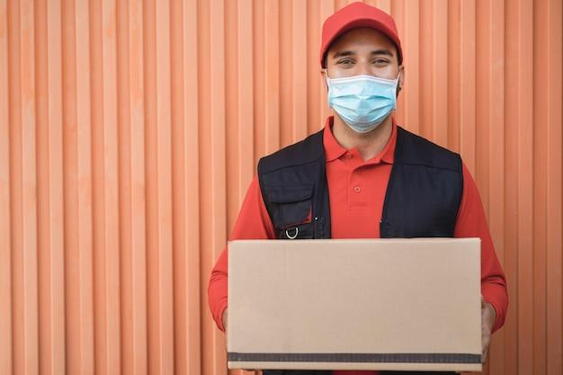 コロナウイルスの発生時に段ボール箱を保持している配達人の肖像画-顔に焦点を当てる