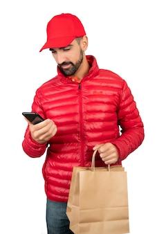 Портрет доставщика, держащего пакет и использующего мобильный телефон на белом фоне