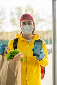 Портрет курьера в маске и желтом пальто, показывающего сообщение на смартфоне во время бесконтактной доставки продуктов