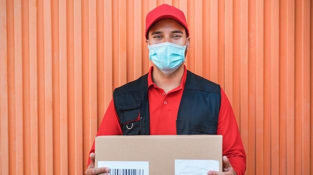 コロナウイルス拡散防止のための顔の保護マスクを身に着けている配達人の肖像-covid 19パンデミック時に仕事で宅配便