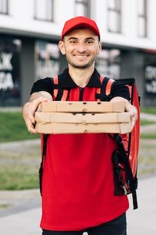 顧客の宅配ファーストフードを待っている熱いピザの箱を持つ配達人の肖像画