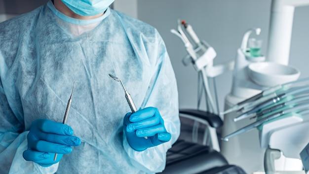 Портрет стоматолога с стоматологическими инструментами в руках