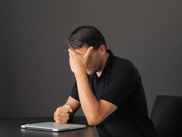 Портрет депрессии и усталости молодого кавказского человека, держаться за руки на лице и вздыхать, чувствовать сожаление или горе, стоя расстроен, чувствуя психическое расстройство, выгорание работы, потеря работы.