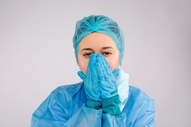 Портрет подавленной женщины-врача в медицинской форме на сером изолированном фоне