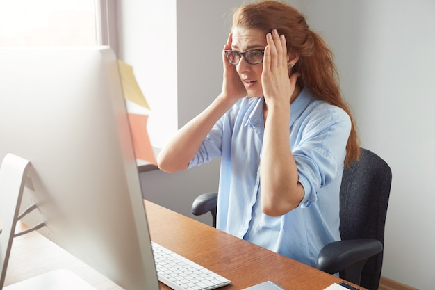 Портрет подавленной женщины-предпринимателя, сидящей перед компьютером во время работы в офисе