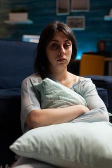 ソファに一人で座っているカメラで見ている落ち込んで脆弱なストレスの多い絶望的な女性の肖像画