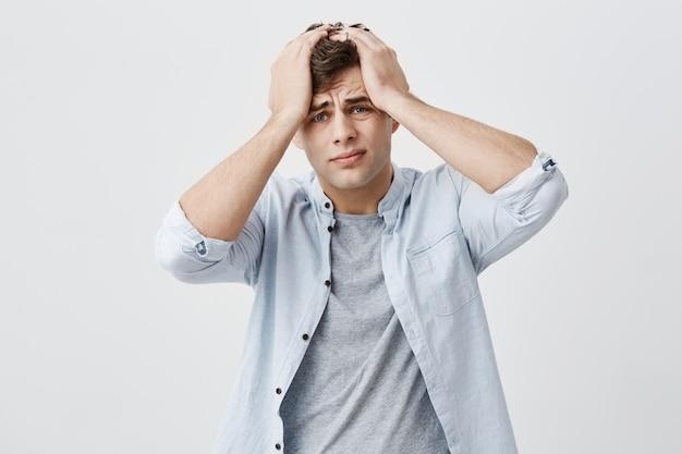 Портрет отчаянно раздраженного уставшего европейского парня нахмурился, положил руки ему на голову, вспомнив, что он о чем-то забыл. отрицательные выражения человеческого лица, эмоции и чувства