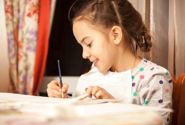 Портрет прилежной девушки рисует кистью