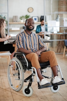 車椅子に座って、オフィスでカメラに笑みを浮かべて障害者のアフリカのビジネスマンの肖像画