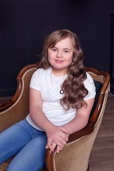 다운 증후군 장애 소녀의 초상화는 흰 벽 위에 절연 포즈를 취하는 동안 카메라에 웃고. 전면보기. 세로 샷.