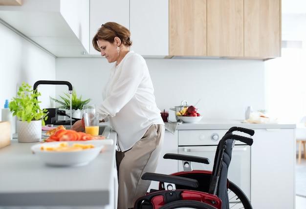 집에서 휠체어를 탄 장애인 성숙한 여성의 초상화, 아침 식사를 준비합니다.