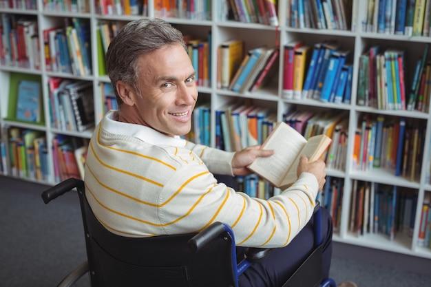 図書館で本を保持している障害のある学校の先生の肖像画