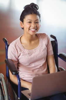 Портрет школьницы-инвалида, использующей ноутбук в кампусе