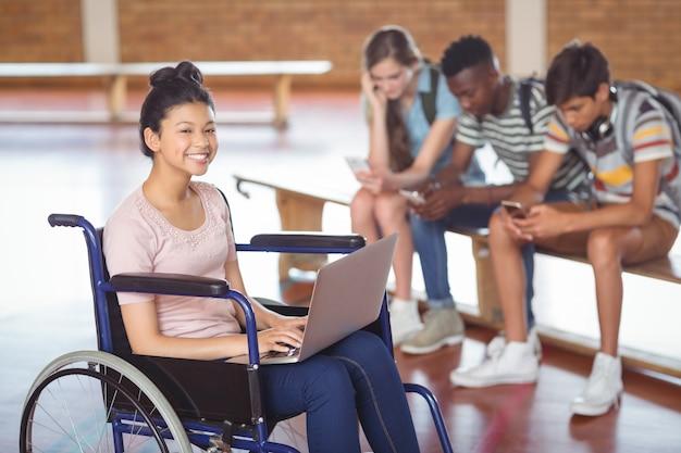 Портрет школьницы-инвалида, использующей ноутбук с одноклассниками в фоновом режиме
