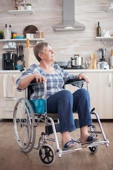 キッチンで迷子に見える車椅子の障害者の不幸な年配の女性の肖像画。負傷とリハビリ、麻痺と悲しみに満ちたうつ病の無効のための障害後の高齢者障害者年金受給者、wo