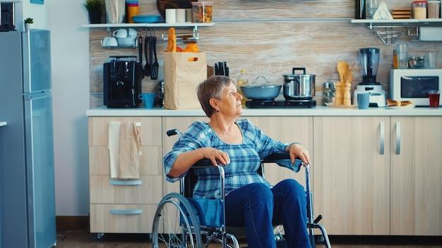Портрет недовольной пожилой женщины-инвалида в инвалидной коляске, выглядящей потерянной на кухне. престарелый пенсионер-инвалид после травмы и реабилитации, паралича и инвалидности из-за депрессии, инвалид, полный печали, wo