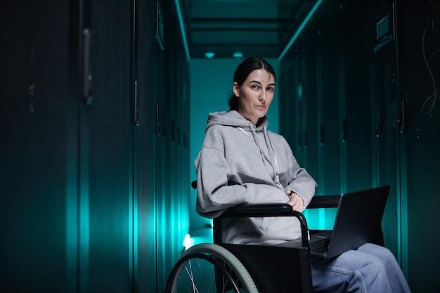 サーバールーム、アクセシブルな仕事の概念、コピースペースでスーパーコンピューターネットワークで作業しながらカメラを見ている車椅子の障害者の女性の肖像画