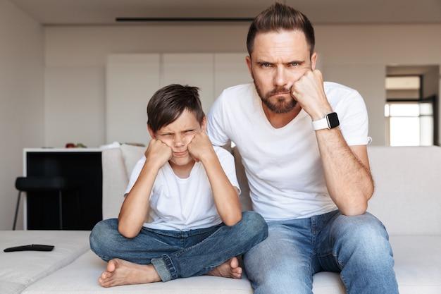 Портрет разочарованных отца и сына, подпирающих голову, сидя на диване в помещении и с нетерпением жду