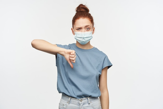 お団子に集まった髪の失望した赤毛の少女の肖像画。青いtシャツと保護マスクを着用しています。不一致で親指を下に表示します。白い壁に隔離
