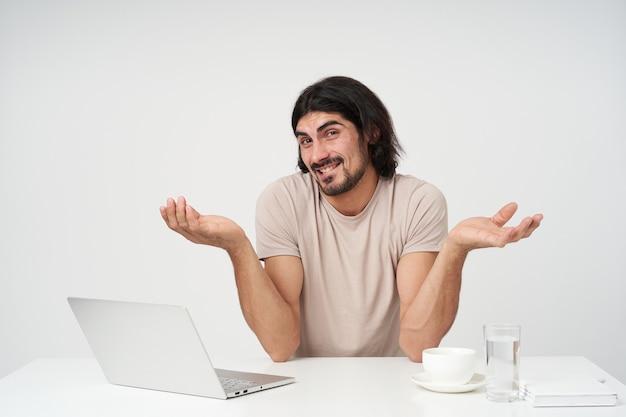 黒髪とひげを持つ不満の実業家の肖像画。オフィスのコンセプト。職場に座っています。肩をすくめ、唇を噛みます。白い壁に隔離