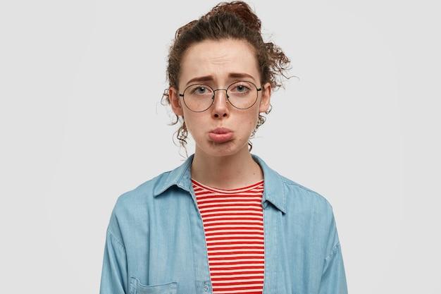 白い壁にポーズをとって眼鏡をかけて不満そばかすティーンエイジャーの肖像画