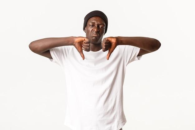 Портрет разочарованного и разочарованного афроамериканского молодого парня, который показывает палец вниз и презрительно гримасничает