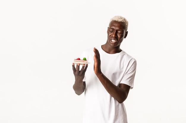 Портрет возмущенного красивого афроамериканского молодого блондина, не желающего есть десерт, съеживающегося от отвратительного торта
