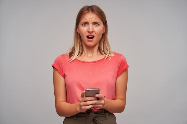 不機嫌な、ブロンドの髪の大人の女の子の肖像画。ピンクのtシャツと茶色のスカートを着ています。携帯電話を持っています。灰色の壁にひどいメッセージを送る