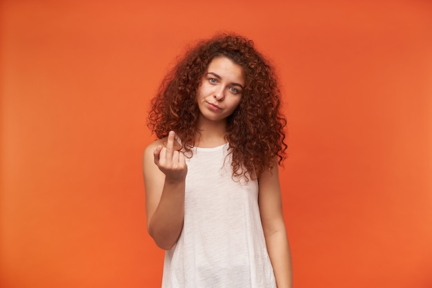 Портрет недовольной, взрослой рыжей девушки с вьющимися волосами. надеть белую блузку с открытыми плечами. показываю знак ебать. отвали. изолированные над оранжевой стеной