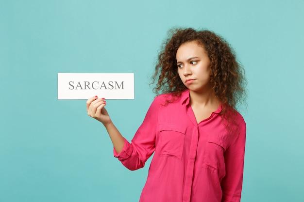 분홍색 캐주얼 옷을 입은 불쾌한 아프리카 소녀의 초상화는 스튜디오의 파란색 청록색 벽 배경에 격리된 sarcasm 텍스트 보드를 들고 있습니다. 사람들은 진심 어린 감정, 라이프 스타일 개념입니다. 복사 공간을 비웃습니다.