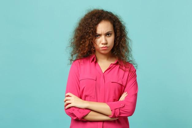 青いターコイズブルーの背景に分離された手を交差させたカメラを探しているピンクのカジュアルな服を着た不機嫌なアフリカの女の子の肖像画。人々の誠実な感情、ライフスタイルのコンセプト。コピースペースをモックアップします。